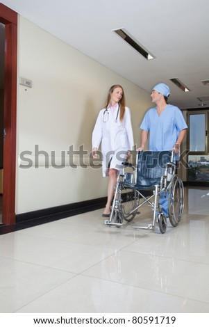 Doctor walking with male nurse pushing wheelchair - stock photo