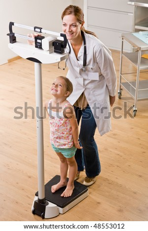 Doctor weighing girl in doctor office - stock photo