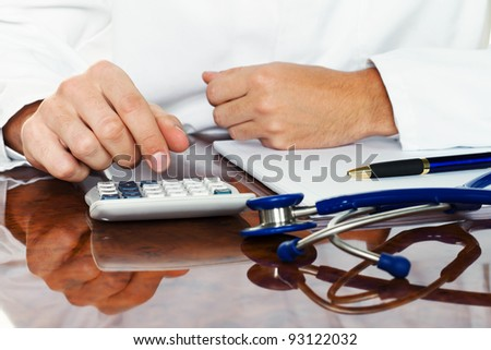 doctor with a calculator. calculation of costs and revenues in physician practice and hospital - stock photo
