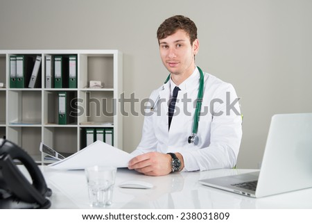 doctor with a medicine documentation smiles - stock photo