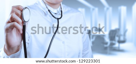 Doctor with a stethoscope in the hands and office background - stock photo