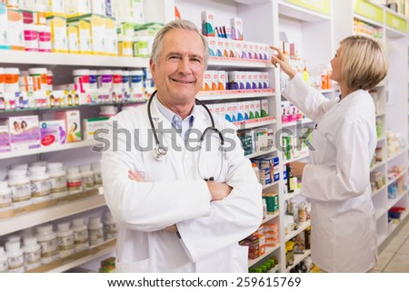 Doctor with arms crossed with colleague behind him in the pharmacy - stock photo