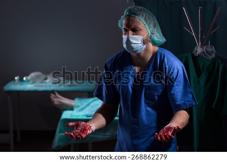 Doctor with bloody hands - metaphor of death by medical mistake - stock photo