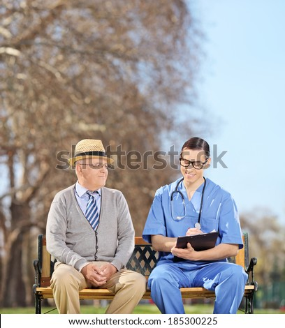 Doctor with clipboard and a senior sitting in park shot with tilt and shift lens - stock photo