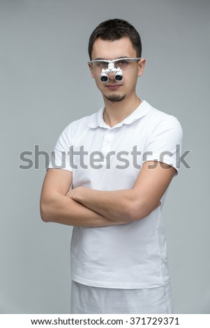 Doctor with dental binocular loupes on his face with a slight smile looking to the camera. He stands with crossed arms on the gray background. Studio photo. Vertical. - stock photo