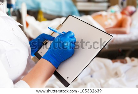 doctor with empty blank clipboard and patient on background - stock photo