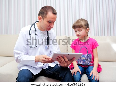 Doctor with girl looking at tablet - stock photo