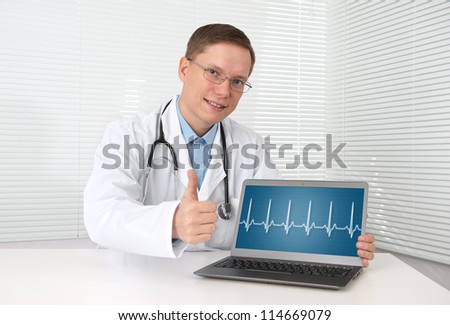 doctor with hearts beat diagram on a laptop computer - stock photo