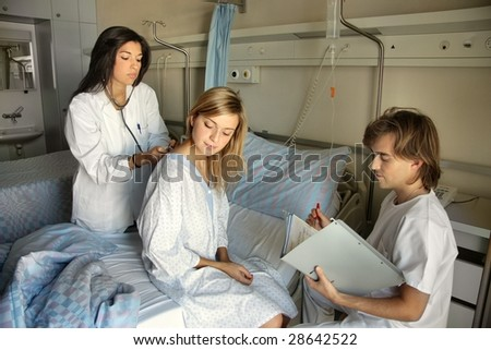doctor with patient and co-worker in a hospital - stock photo