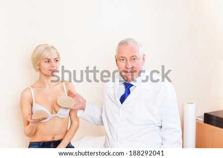 doctor with patient, show breast implant, plastic surgery clinic young girl - stock photo