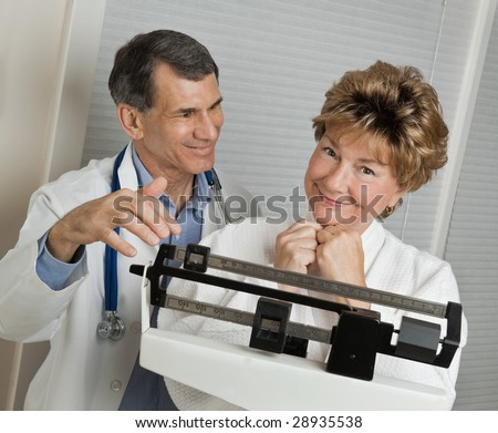 Doctor with smiling woman who has reached her target weight on medical scale in doctor's office. - stock photo