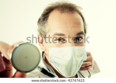 Doctor with stethoscope and flu mask. - stock photo