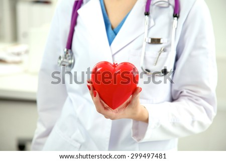 Doctor with stethoscope examining red heart - stock photo