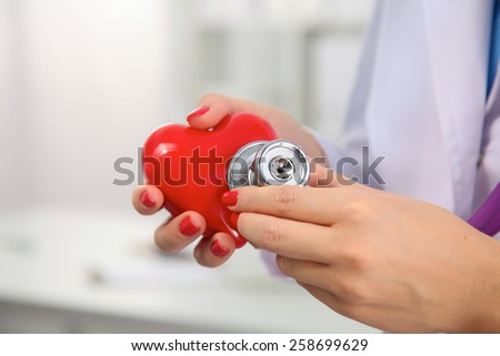 Doctor with stethoscope examining red heart, isolated on white background