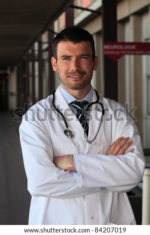 doctor with stethoscope in front of hospital entry - stock photo