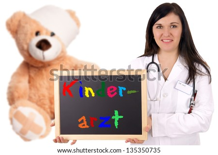 Doctor with teddy and shield with the german words Pediatrician / Pediatrician - stock photo