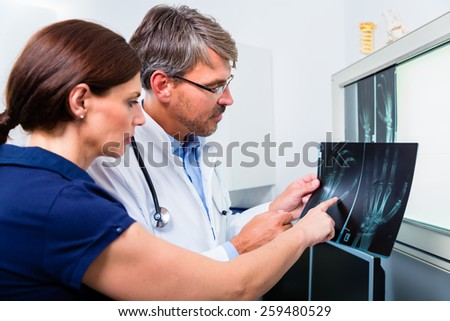 Doctor with x-ray picture of patient hand in his surgery examining the image - stock photo