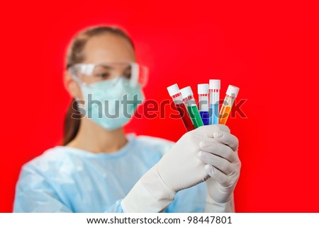 Doctor (woman) analyzing medical test tubes on red background - stock photo