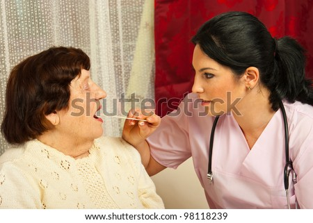 Doctor woman examine elderly patient for sore throat in her house - stock photo