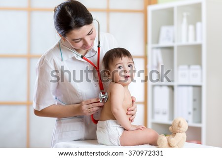 doctor woman examining lungs of kid with stethoscope - stock photo