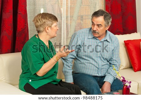 Doctor woman having conversation with mature man in his home