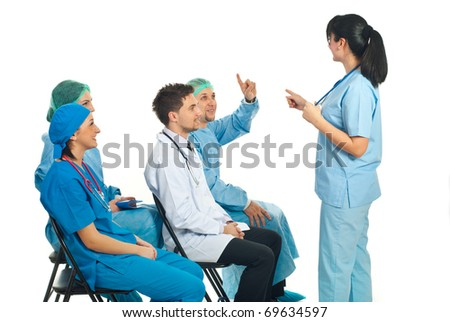 Doctor woman pointing to a surgeon man with hand raised who know the answer to question at conference - stock photo