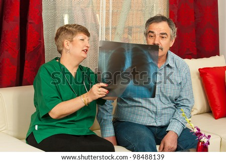 Doctor woman showing x-ray to surprised mature patient male in his home