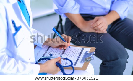 Doctor woman sitting with  male patient at the desk - stock photo