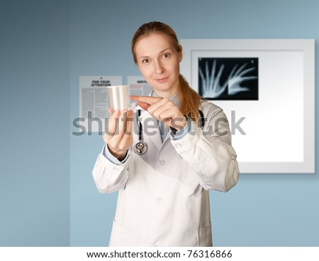 doctor woman with cup for analysis - urine, sperm - stock photo