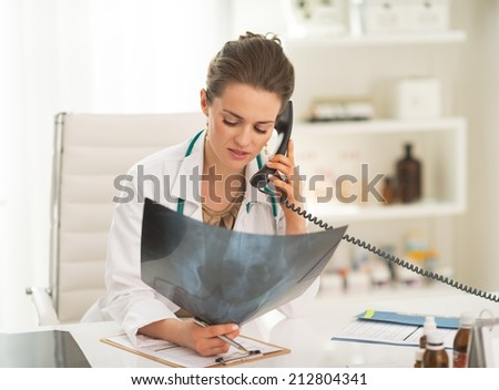 Doctor woman with fluorography talking phone - stock photo