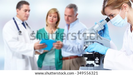 Doctor woman working with microscope. Health care background. - stock photo