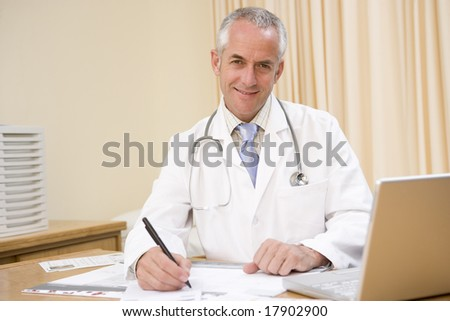 Doctor working at desk - stock photo