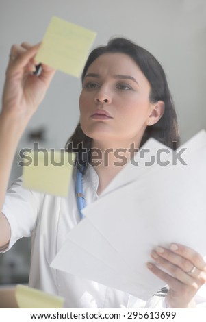 Doctor working at office with patient symptoms and test results - stock photo