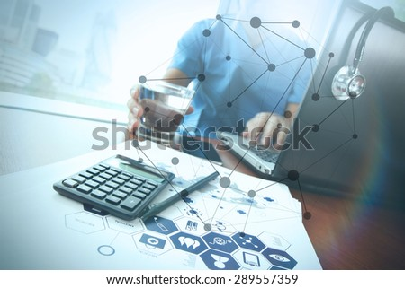 Doctor working at workspace with laptop computer in medical workspace office and medical network media diagram as concept - stock photo