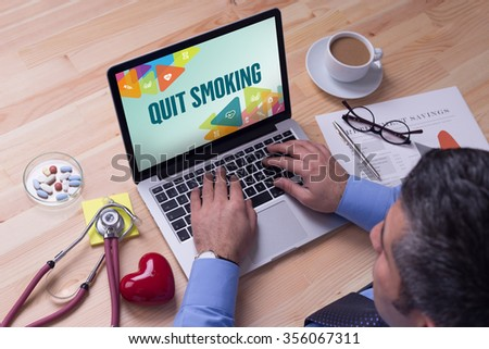 Doctor working on a laptop and QUIT SMOKING on his screen - stock photo