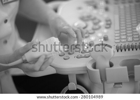 Doctor working with a diagnostic ultrasonography machine - stock photo