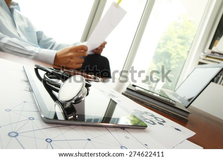 Doctor working with digital tablet and laptop computer in medical workspace office and medical network media diagram as concept - stock photo