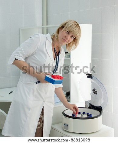 Doctor working with electronic blood centrifuge in medical clinic - stock photo