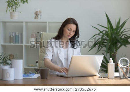 Doctor working with laptop computer at her office - stock photo