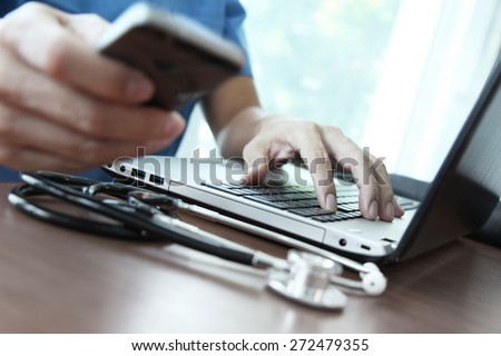 Doctor working with laptop computer in medical workspace office and picking smart phone as concept - stock photo