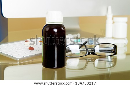 Doctor workplace. Pills, tablets, bottle, computer, glasses - stock photo
