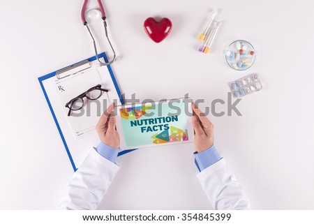Doctor workplace with NUTRITION FACTS on tablet - stock photo