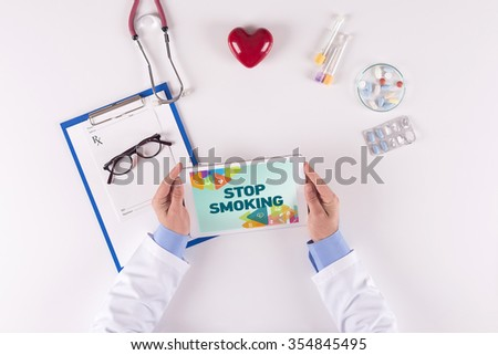 Doctor workplace with STOP SMOKING on tablet - stock photo