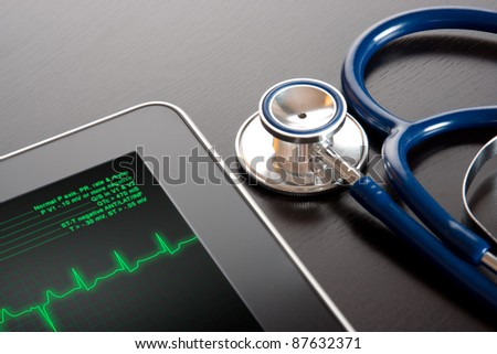 Doctor workplace with tablet display electrocardiogram (ECG) and stethoscope