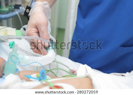 Doctor works with patient in the intensive care unit ward - stock photo