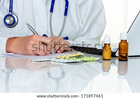 doctor writes a prescription for tablets. in the doctor's office - stock photo