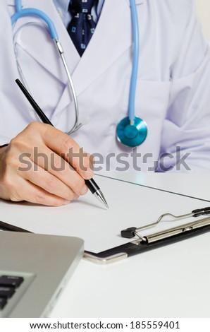 Doctor writing a prescription - stock photo
