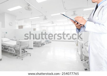 doctor writing clipboard for diagnosis in aided the recovery room with modern equipment and comfortable equipped in hospital - stock photo