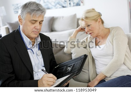 Doctor writing medical presciption to patient - stock photo