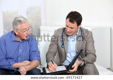 Doctor writing medical prescription to elderly man